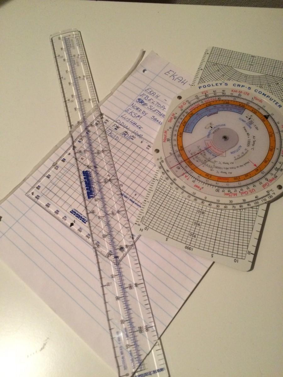 Drejecomputer til venstre sammen med tilhørende lineal der måler i nautiske mil